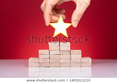 Person Placing Star On Top Of Stacked Wooden Blocks Stock photo © AndreyPopov