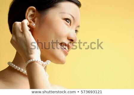 Gyönyörű fiatal ázsiai nő visel fülbevalók Stock fotó © dolgachov