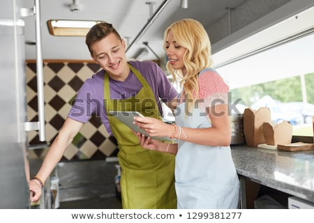 couple of sellers with tablet pc at food truck Stock photo © dolgachov