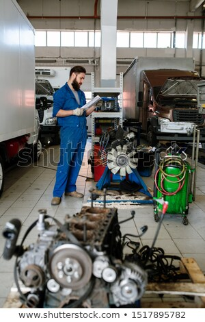 Young worker of technical maintence service standing by one of machines Stock photo © pressmaster