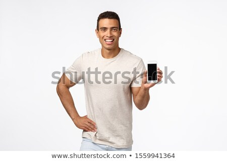 Proud and assertive handsome hispanic man in t-shirt, holding smartphone, promote application or sho Stock photo © benzoix