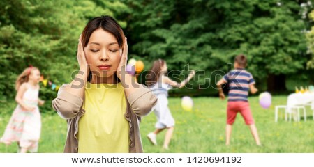 asian woman closing ears over kids party at park Stock photo © dolgachov