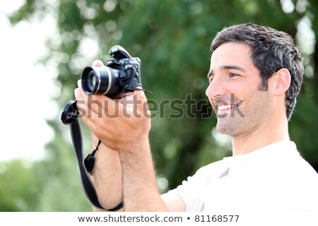 Stock photo: Happy relaxed man looking at the screen of his DSLR camera as he takes a photograph
