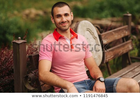 smiling beautiful couple sitting on a banch at summer park and d stock photo © hasloo