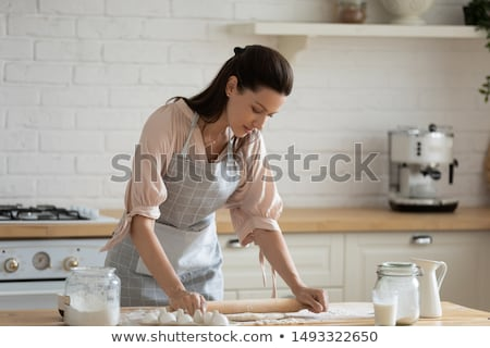 young woman using rolling pin on dough stock photo © rob_stark