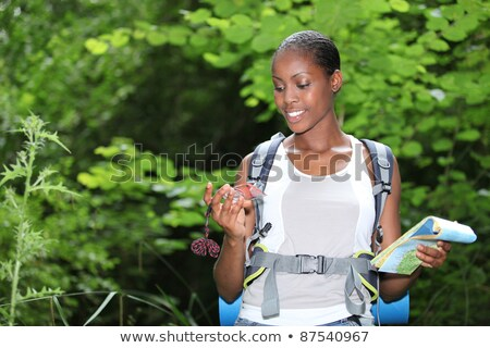 woman stood outdoors holding compass and map stock photo © photography33