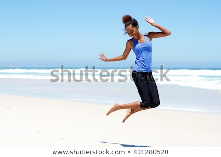 cheerful woman jumping laughing at beach portrait stock photo © juniart