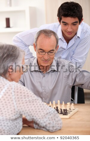 Young man watching an older couple play chess Stock photo © photography33