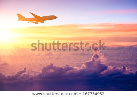 Stock photo: Airplane in the sky at sunset. A passenger plane in the sky
