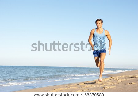 young man in fitness clothing running along beach stock photo © monkey_business