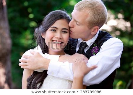 Caucasian groom lovingly kissing his biracial bride on cheek. Di Stock photo © jarenwicklund