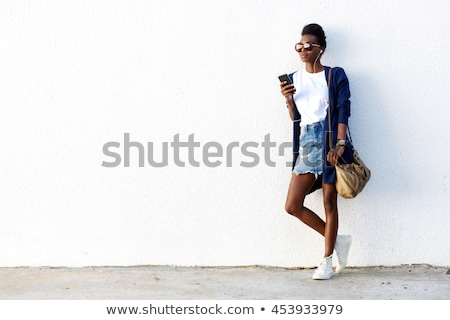 attractive lady standing and leaning against white wall while po Stock photo © feedough