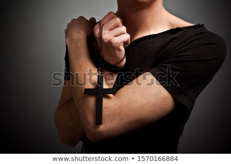 Priest holding rosary and praying with eyes closed  Stock photo © deandrobot