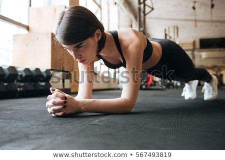 Sportswoman doing plank exercise in gym Stock photo © deandrobot