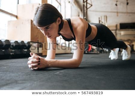 sportswoman doing plank exercise in gym stock photo © deandrobot