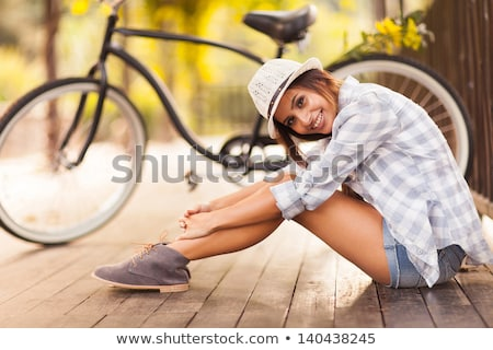 Young beautiful woman sitting on her bicycle with flowers at sun Stock photo © vlad_star
