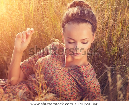 young beautiful girl lying at yellow autumn field stock photo © massonforstock
