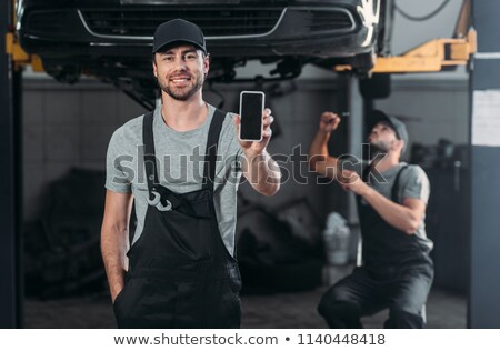 auto mechanic with smartphone at car service Stock photo © dolgachov