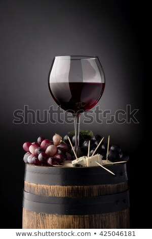Elegant glass of red wine with dark and red and green grapes on wooden board on black background. Sp Stock photo © DenisMArt
