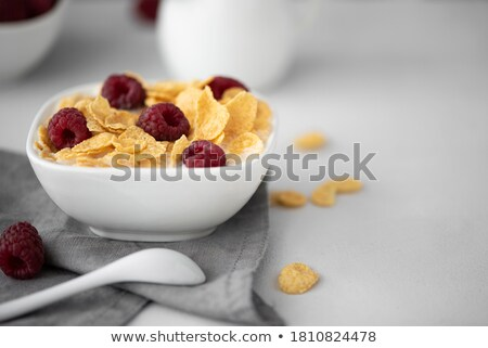 Golden cornflakes with fresh fruits of raspberries, blueberries and pear in ceramic bowl Stock photo © dash