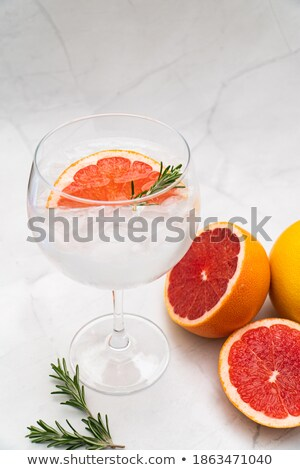 glass of orange soda drink with ice cubes and white bowl of popcorn snack on stone kitchen table bac stock photo © denismart