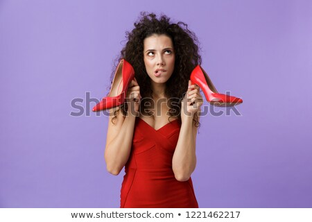 Image of caucasian woman 20s wearing red dress holding high heel Stock photo © deandrobot