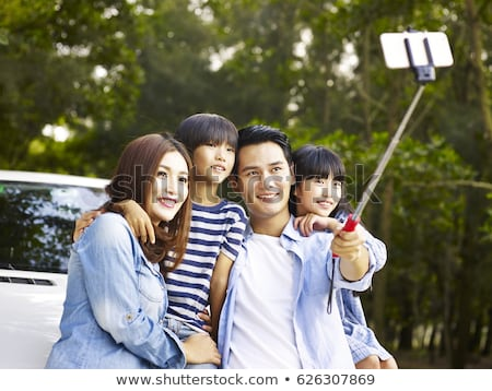 woman taking picture by selfie stick at car Stock photo © dolgachov