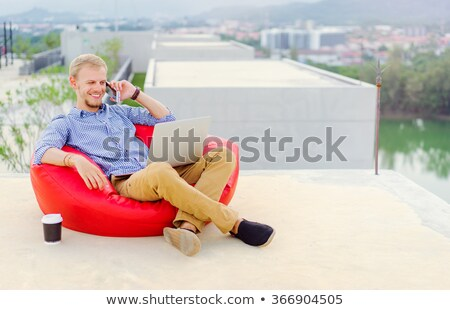 Stock photo: Handsome young business man sitting outdoors using laptop computer.
