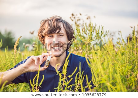 Young man uses a spray from an allergy because of an allergy to ragweed Stock photo © galitskaya