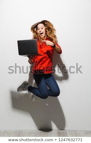 Full length photo of pretty woman 20s wearing red sweatshirt jum Stock photo © deandrobot