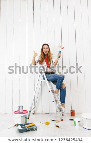 Full length photo of european woman 20s sitting on ladder and pa Stock photo © deandrobot
