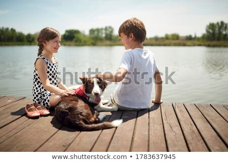 Cute childs brother and sister sitting on a wooden platform by the lake. Stock photo © Lopolo
