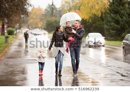 Stock photo: A Father And Child On A Rainy Day In A Park With Umbrella