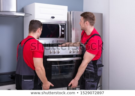 Foto stock: Young Male Worker Placing Modern Oven In Kitchen