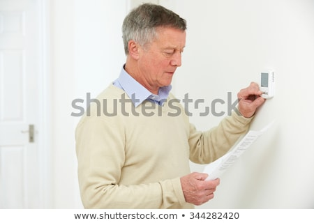 Senior Man Adjusting Central Heating Thermostat Stock photo © HighwayStarz