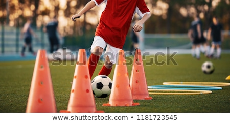 Soccer training practice. Player running with football ball in sports grass cleats. Training session Stock photo © matimix