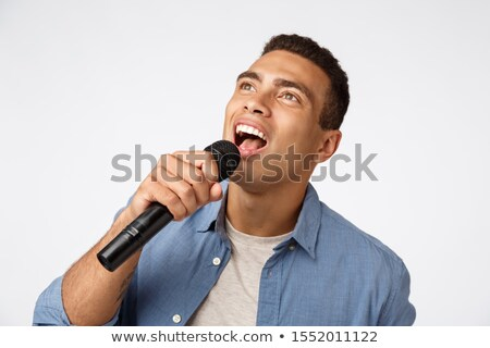 Carefree good-looking young man having fun during christmas party, singing favorite song, hold micro Stock photo © benzoix