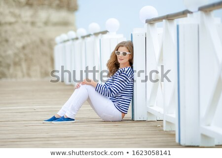 Adult caucasian women sit on rocky beach with blue neckchief relaxing and thinking about something. Stock photo © ElenaBatkova