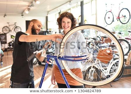 Happy woman working as a bicycle mechanic Stock photo © Kzenon