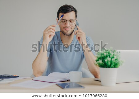Busy male works on organizational issues, speaks with business partner via cell phone, keeps eyes cl Stock photo © vkstudio