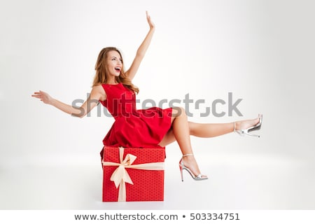 Stock photo: Red-haired girl in dress with present box at white background.