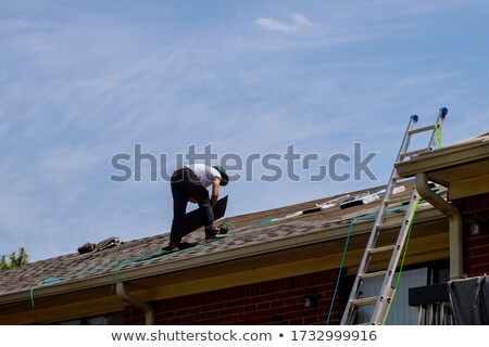 Stock photo: Roofer about to replace tiles