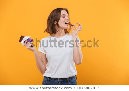 Pretty young woman eating chocolate Stock photo © Nobilior