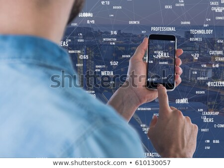 Stock photo: Holding mobile phone against Night city with connectors