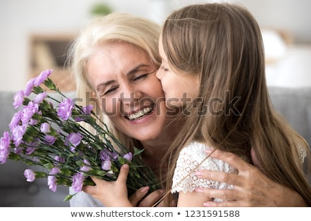 granddaughter kissing grandmother on cheek holding flowers and s stock photo © monkey_business