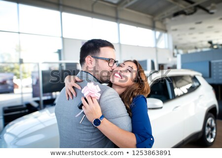 happy cheerful couple celebrating new car purchase stock photo © deandrobot