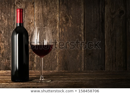 Elegant glass of red wine on wooden board on black background.  Stock photo © DenisMArt