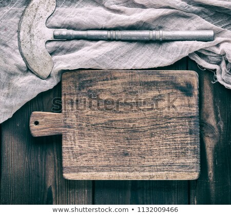 vintage wooden cutting board with towel and meat hatchet on top of black stone kitchen stone backgro stock photo © denismart