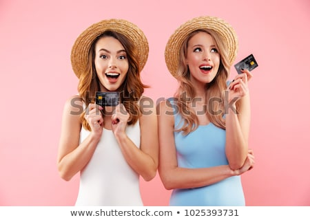 Image of two beautiful women smiling and holding credit cards, i Stock photo © deandrobot