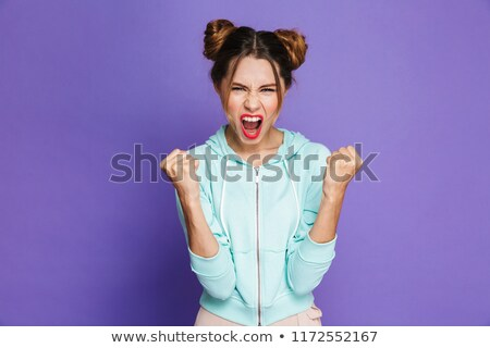 Portrait of cheerful pretty woman with two buns rejoicing and cl Stock photo © deandrobot